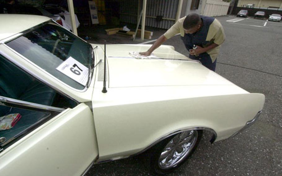 Staff Sgt. Dwyane Harvin polishes his 1967 Oldsmobile Cutlass for a competition at the car show.