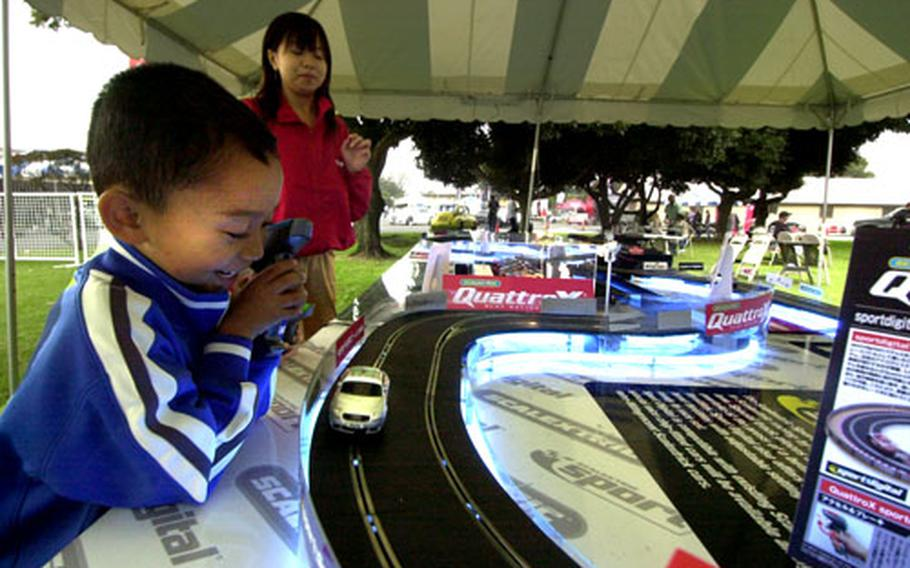 Nathan Castillo plays with an electric race track set at the Yokota car show.