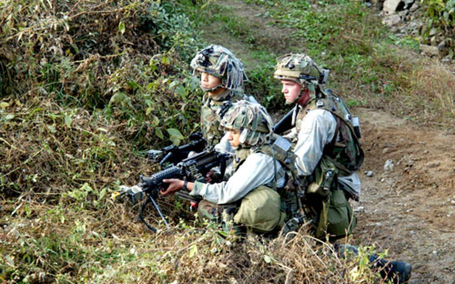 Soldiers from Company A, 2nd Battalion, 9th Infantry Regiment wait to ambush Bradley Fighting Vehicles and tanks from Task Force 2nd Battalion, 72nd Armored Regiment at Twin Bridges Training Area on Friday.