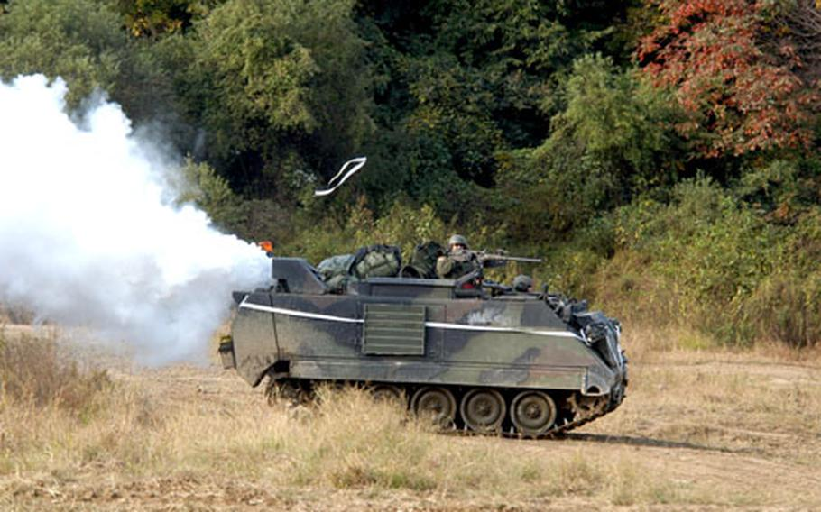 An M-113 Armored Personnel Carrier blows smoke to simulate a chemical barrage.