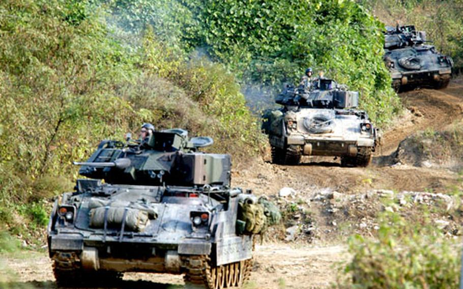 """Task Force 2nd Battalion, 72nd Armored Regiment Bradley Fighting Vehicles move towards the """"enemy"""" at Twin Bridges Training Area on Friday."""