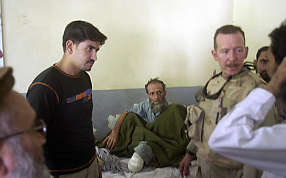 Capt. Todd Tarner, right, talks with doctors at the hospital Wednesday afternoon in Afghanistan.