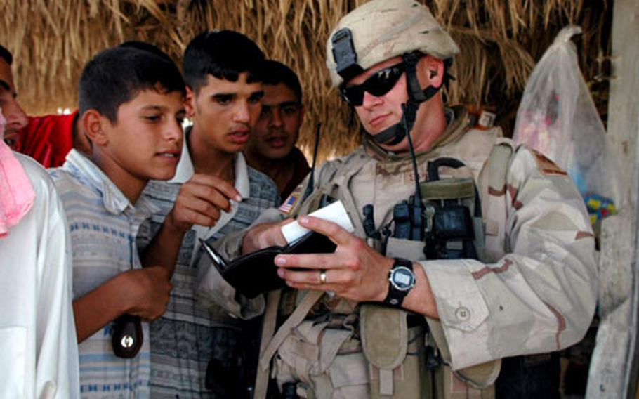 Locals in Mushada, Iraq, look at family photos from Capt. Gregory Spencer. Despite being open in their criticisms of Americans, many Iraqis have a playful relationship with U.S. soldiers.