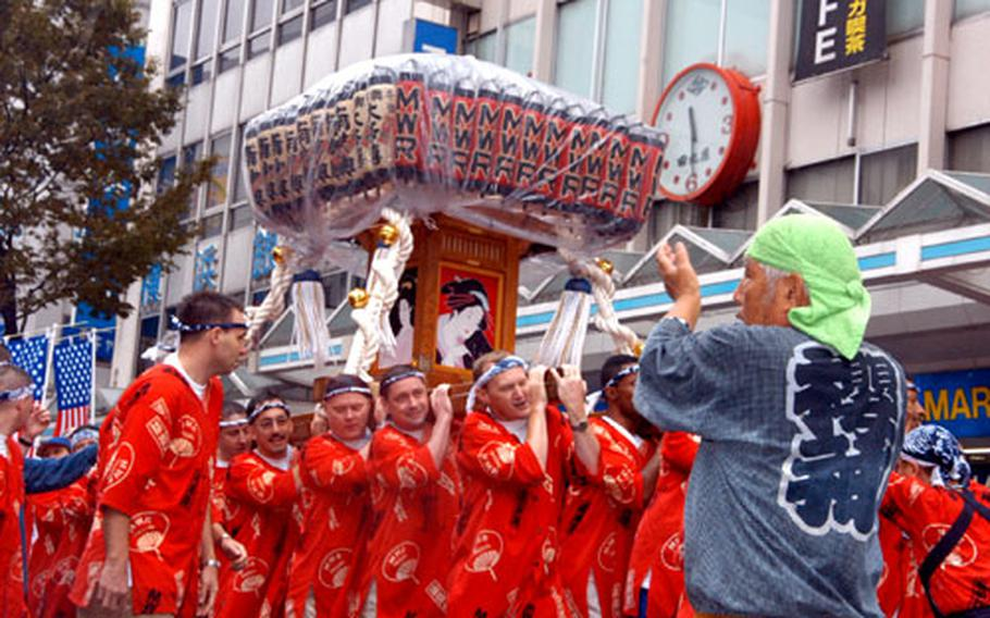"""More than 160 Americans from Yokosuka Naval Base volunteered to carry the """"Gaijin"""" altar during Yokosuka's Mikoshi Parade on Sunday. More than 70 heavy altars were shouldered and danced through the city to the base to bring good luck in the coming year."""