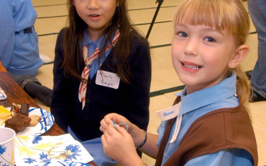 Yokosuka residents Isabella Back and Misato Yoshigaki pledged to be sisters Sunday in an international collaboration between USA Girl Scouts Overseas and Japanese Girl Scouts.
