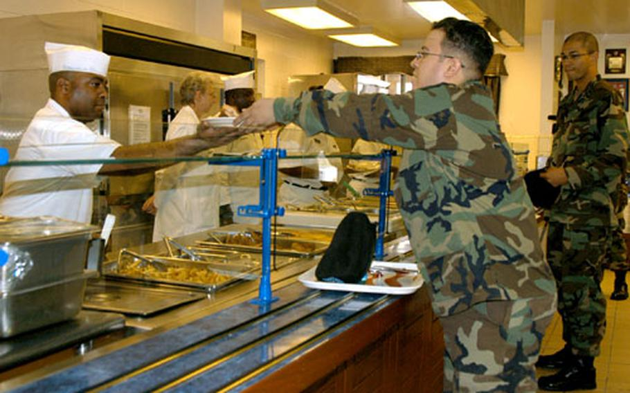 Spc. Jermaine Jackson, 32, of Talladega, Ala., hands a soldier his lunch. Jackson was in charge of the fryer and short-order cooked items Thursday, including chicken, fries and grilled cheese sandwiches.