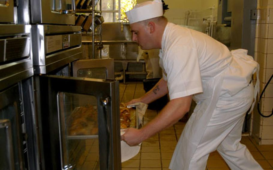 """""""Hot pan! Hot pan!"""" Spc. Christopher Yingling, 25, of Blackstone, Va., pulls a sheet of glazed cornish game hens from an oven to see how much longer they need to cook."""