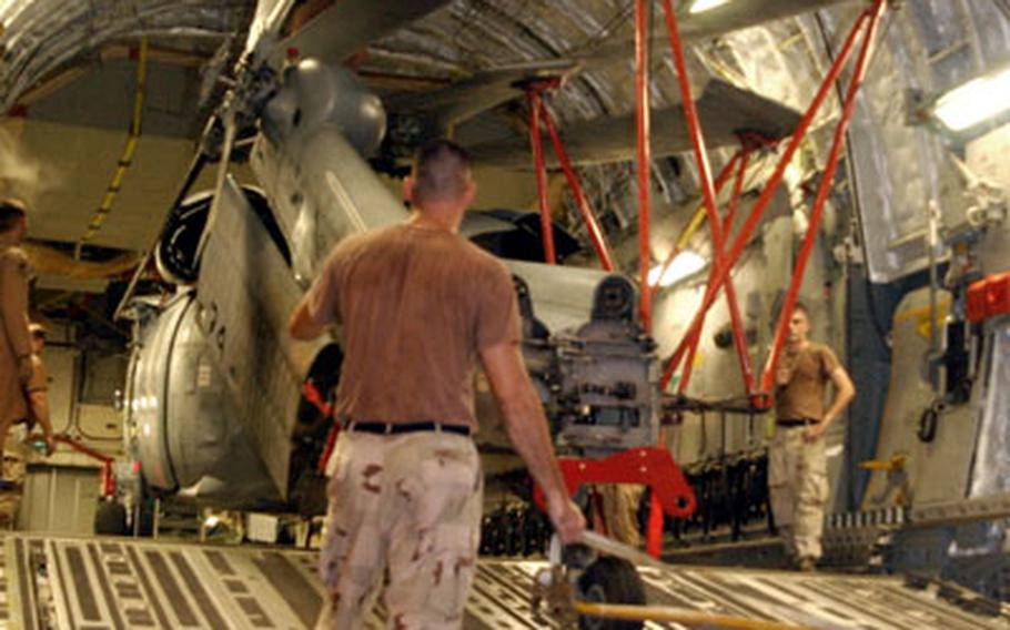 A sailor controls the tension and direction of an MH-60S Seahawk helicopter as it is loaded Monday onto a U.S. Air Force C-17 Globemaster III in Manama, Bahrain. The Seahawk will help deliver medical supplies, water and tents to earthquake victims in Pakistan. The squadron will deploy 25 sailors and two MH-60S helicopters to help those in need in Pakistan.