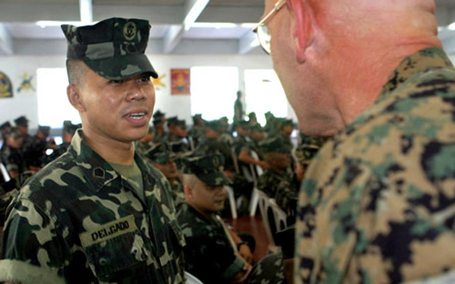 U.S. Marine Sgt. Maj. James R. McKay, right, greets Philippine Marine Sgt. Jonathan S. Delgado during the opening ceremony for a bilateral training evolution taking place in the Philippines.