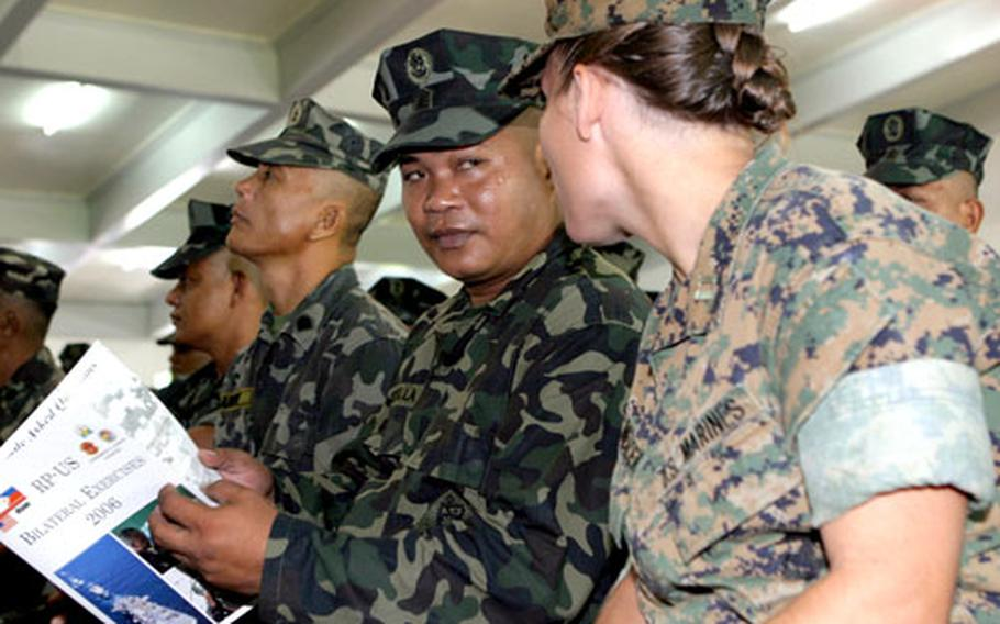 Capt. Jennifer A. Mercer, right, the supply officer with the 31st Marine Expeditionary Unit, talks with a Philippine marine.
