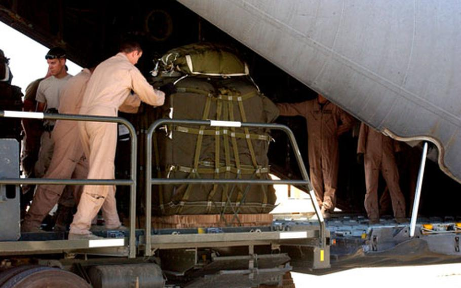 Servicemembers at Bagram Air Base push a pallet full with humanitarian aid supplies into a C-130 on Oct. 13.