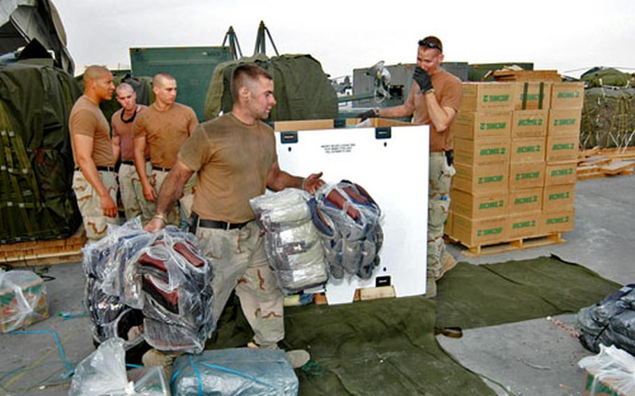 Spc. Bryan Jackson, front, and other parachute riggers with Logistical Task Force 307, based out of Bagram Air Base load pallets with humanitarian supplies this week. The supplies are supposed to be air-dropped into remote areas of Pakistan ravaged by the recent eathquake, but the mission has been delayed four times so far.