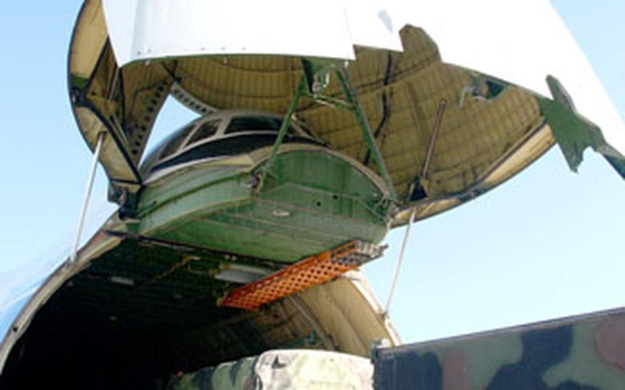 A 5-ton truck from the 212th Mobile Army Surgical Hospital, Miesau, Germany, drives into the belly of a Russian AN-124 Condor cargo aircraft.