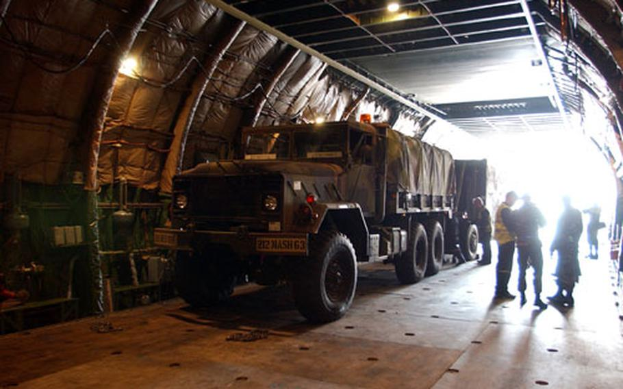 A 5-ton truck from the 212th Mobile Army Surgical Hospital rests in the belly of a Russian AN-124 Condor cargo aircraft.