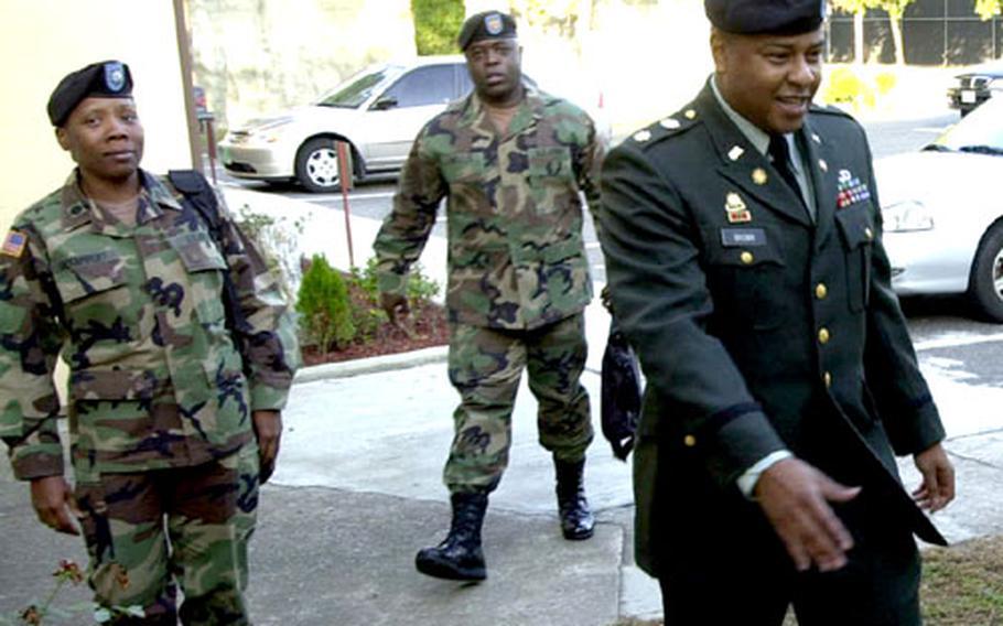 Maj. Jeffrey L. Brown, right, arrives at court Monday morning at Camp Henry, South Korea.