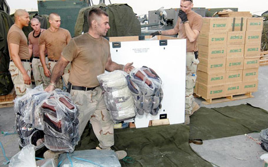 Spc. Bryan Jackson, front, and other parachute riggers with Logistical Task Force 307, based out of Bagram Air Base, Afghanistan, load pallets with humanitarian supplies this week.