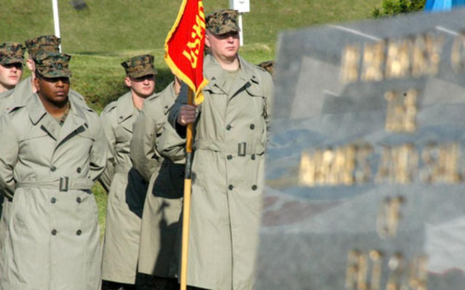 Marines from Camp Fuji's Combined Arms Training Center stand solemnly near the fire memorial marker at Wednesday's annual ceremony at the base flagpole. The observance marked the Oct. 19, 1979, blaze that killed 13 Marines and injured dozens more.