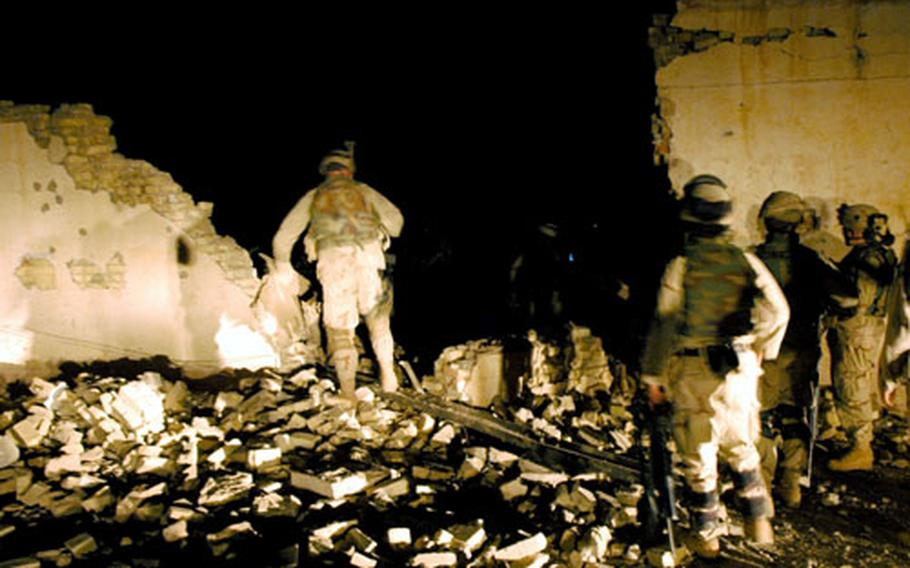 U.S. soldiers do a damage assessment after two 500-pound bombs were dropped on an abandoned slaughterhouse outside Muqdadiyah. Soldiers said the structure was a staging area for insurgents planting roadside bombs.