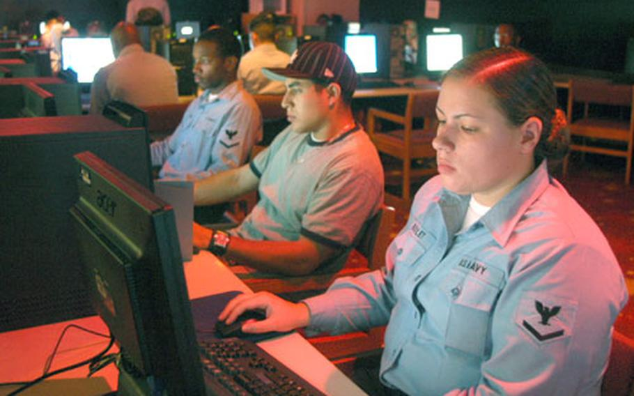 Web-based e-mail restrictions on Navy computers won't impact the access at Yokosuka Naval Base's Single Sailor Liberty Lounge where, from right, Petty Officer 3rd Class Jeanna Boulet, Airman Migual Liera and Petty Officer 3rd Class Dushawn Harris logged computer time Thursday.