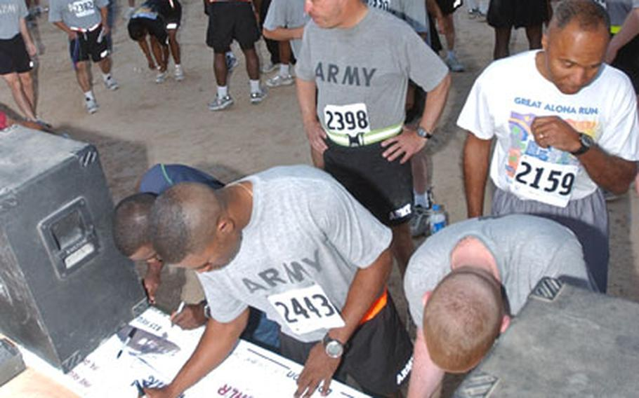 Runners sign a banner before the Big Easy 5K run Oct. 16 at Forward Operating Base Speicher near Tikrit, Iraq.