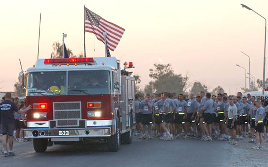 Runners line up behind a Forward Operating Base Speicher fire engine before the start of the Big Easy 5K Run.