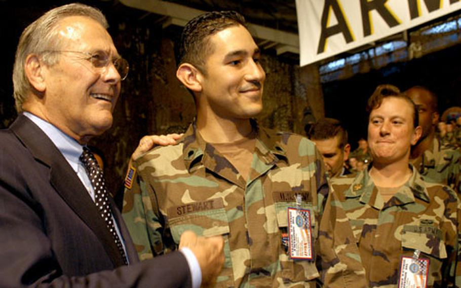 Spc. Sean Stewart, of Tujunga, Calif., poses for a picture with U.S. Secretary of Defense Donald Rumsfeld. After taking questions Friday afternoon, Rumsfeld walked the room, shaking hands and posing for pictures with servicemembers.