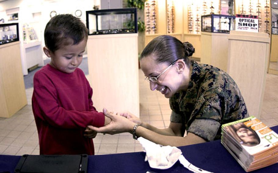 Rudy Rodriguez, 4, lets Sgt. Elizabeth Lopez from MCAS Iwakuni's Provost Marshal's Office take his fingerprints inside the Marine Corps Exchange Thursday.