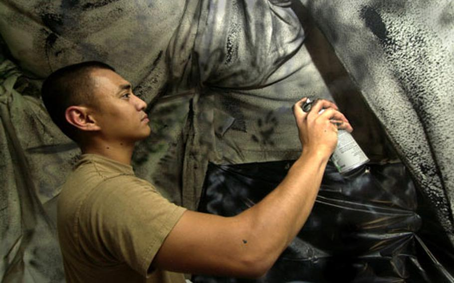 Petty Officer 2nd Class John Cid spray-paints the inside of a haunted house in preparation for Halloween on Naval Air Facility Atsugi, Japan.
