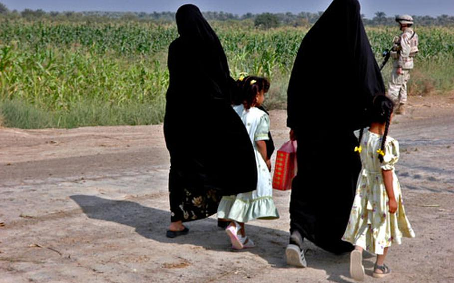 Iraqi women and children walk past a U.S. Army patrol south of Baghdad.