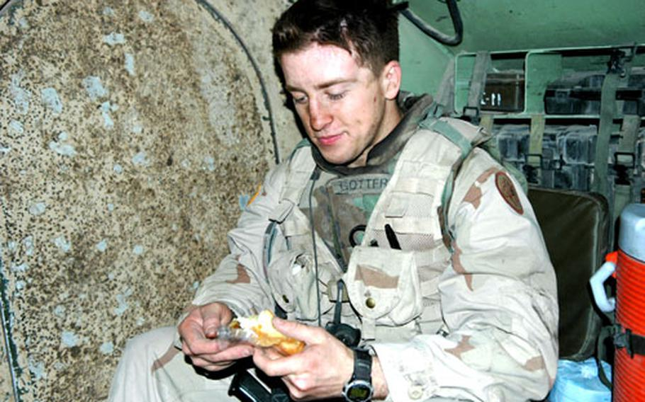 """Pfc. Caleb Gottfried, 21, a medic from San Luis Obispo, Calif., eats a Twinkie after his Bradley was hit by a roadside bomb. No major injuries were reported. Gottfried, like many younger soldiers, referred to the strikes as being """"blown up."""" This is the second time he's been """"blown up,"""" he said."""