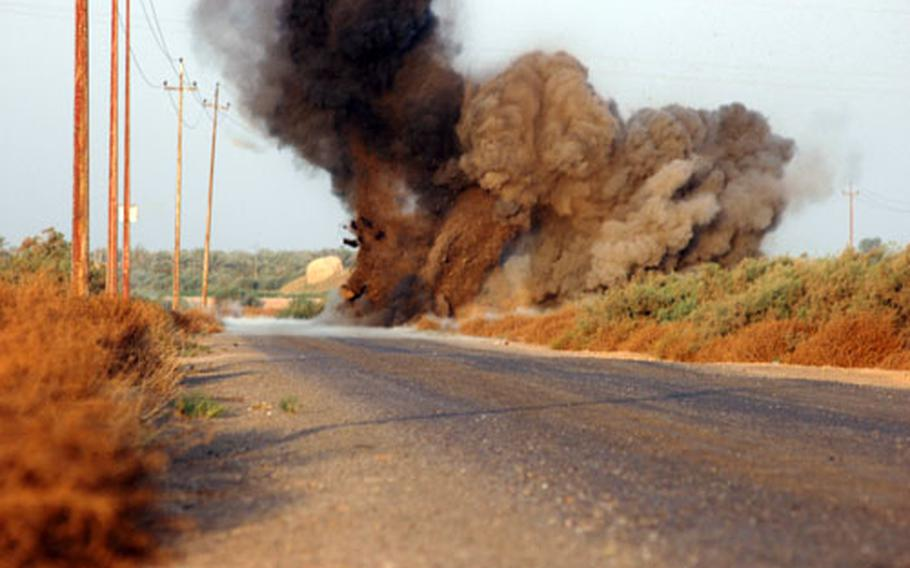 Members of a Navy Explosive Ordnance Disposal team detonate a roadside bomb found by members of 3rd Squadron's Troop I. This bomb, which consisted of three 130-mm rounds, sent up a plume of smoke 100 feet high, members of the team said.