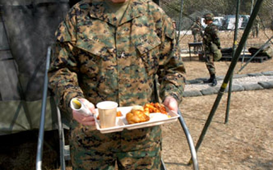 Civilian hospitality consultant Art Ritt prepares to sample a meal produced by soldiers from the 501st Corps Support Group for the Philip A. Connelly field kitchen contest at North Star Range on Wednesday.