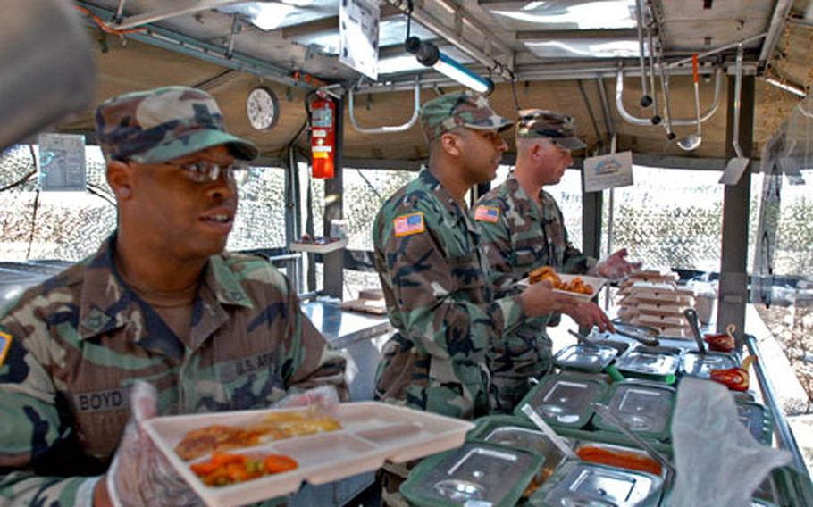 A 501st Corps Support Group soldier, Pfc. Kenyaro Boyd, 31, of Albany, Ga., left, prepares a meal during the Philip A. Connelly field kitchen contest at North Star Range on Wednesday.