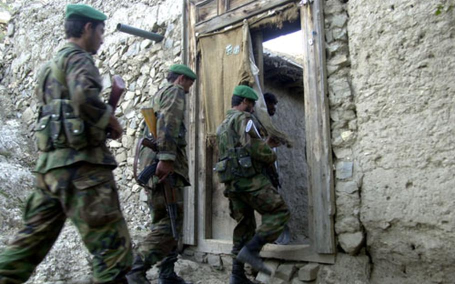 Members of the Afghan National Army search a house in eastern Afghanistan's Kunar province Friday during Operation Pil, a seven-day U.S. Marine battalion-size operation aimed at disrupting insurgents. Marines asked permission to search the houses before sending ANA soldiers into the residences.