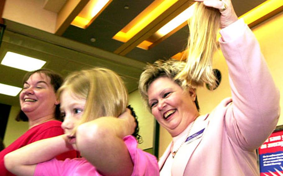 """Richelle Baldwin gets her hair cut off Saturday morning by Flishia Bailey, AAFES general manager, to give to """"Locks for Love."""""""