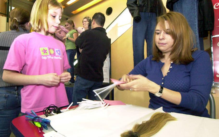 """Richelle Baldwin gives her hair to Callie Mcbee Saturday morning to send to """"Locks for Love."""""""