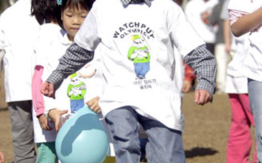"""A Sung Ro Won orphan kicks a soccer ball toward the goal during the """"Watchpup Olympics,"""" on Sunday at Yongsan Garrison, South Korea. The base adopted the orphanage four months ago. Sunday was the children's first visit to the base."""