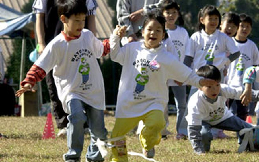 """Young orphans compete in the """"three-legged"""" race."""
