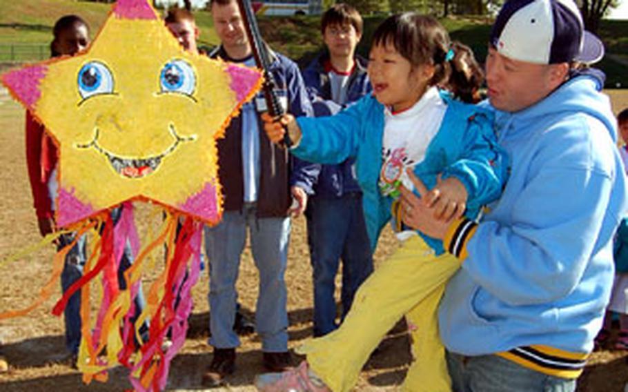 Sgt. Jimmy Ward helps an orphan hit a star-shaped pinata Sunday.