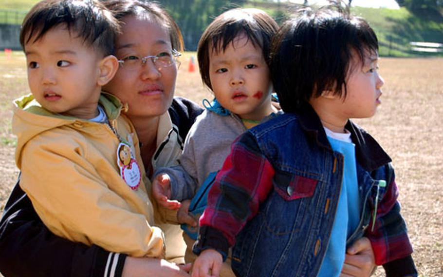 An instructor working in the Sung Ro Won orphanage hugs her kids.