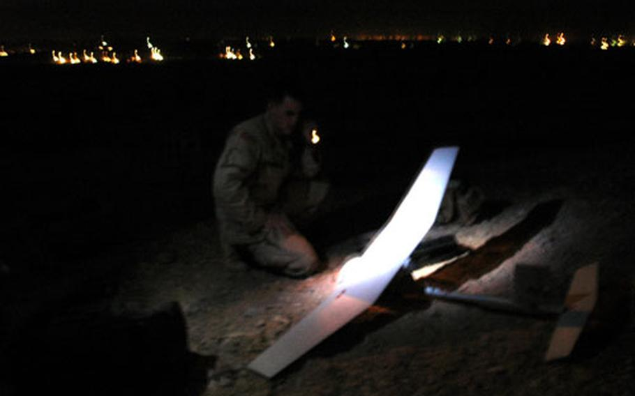 Spc. Coby Harris sets up a Raven unmanned aircraft before launching it for a surveillance mission over a road where insurgents have been setting roadside bombs.