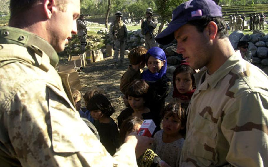 U.S. Navy Hospital Corpsman 3rd Class Michael Johnson, left, tells a interpreter the daily dosage of medication children attending a medical civil assistance program Saturday in Watapoor, Afghanistan, should take. The MEDCAP was the capstone mission during Operation Pil, a seven-day U.S. Marine battalion-size operation in eastern Afghanistan's Kunar province.