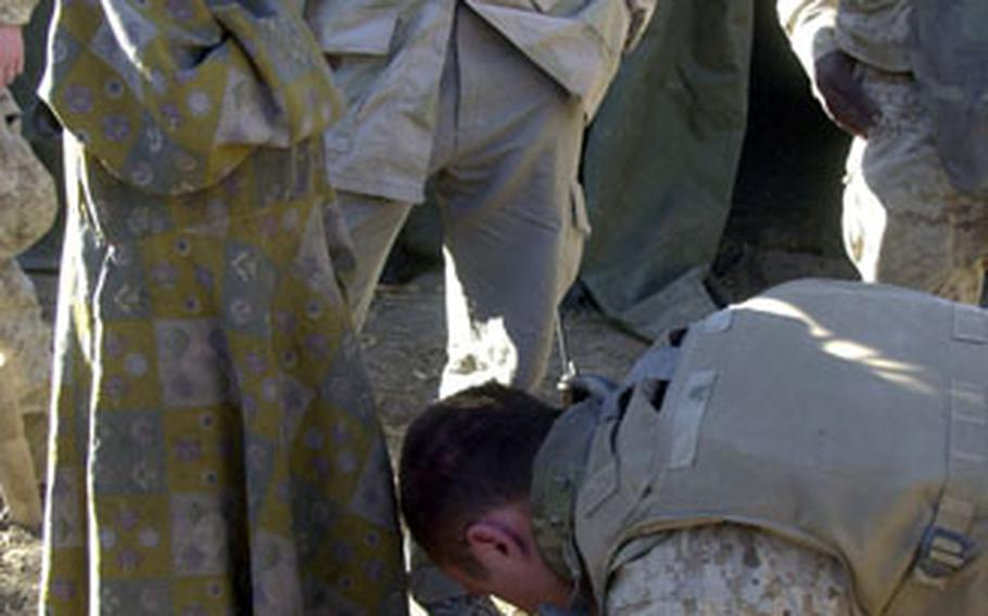 U.S. Navy Hospital Corpsman 3rd Class Michael Johnson treats an Afghan girl's scraped toe Saturday during a medical civil assistance program in Watapoor, Afghanistan.
