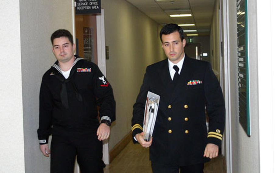 Petty Officer 3rd Class David Fail, left, walks to the courtroom with his lawyer, Lt. Michael Arcati, at Naval Support Activity Naples, Italy, on Monday morning.
