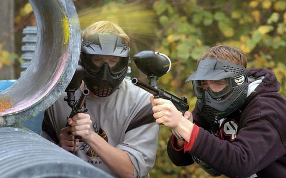 Aaron Reott, left, and James Christensen take cover as a paint ball explodes just over their heads at the paint ball field in Griesheim, Germany. The 233rd Base Support Battalion out of Darmstadt, Germany, recently won the Outstanding Installation Recreation Program in the U.S. Army for medium-sized installations.