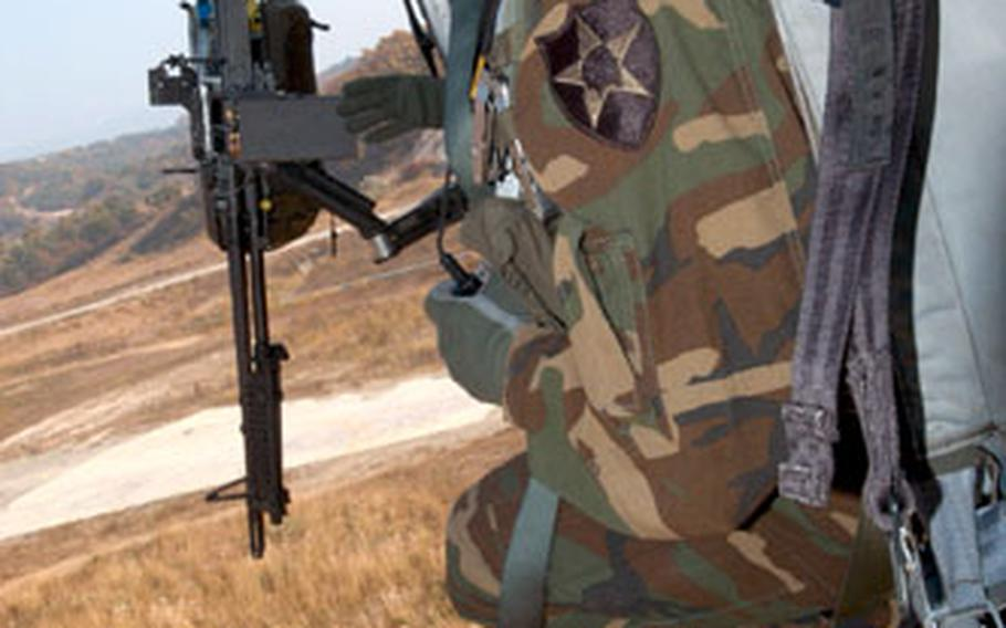 A 2-2 soldier hangs out the door of a Black Hawk helicopter.