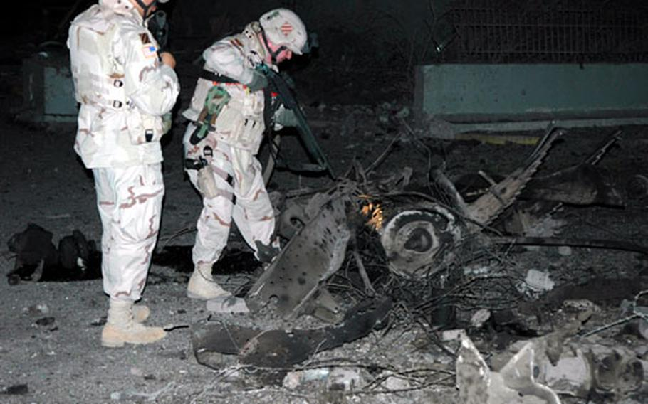 Soldiers examine the ruins of one of the vehicles used as a mobile bomb in Baghdad just hours after the attack on two hotels Monday night.