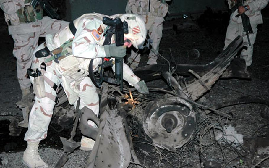 Third Infantry Division soldiers Monday night examine the ruins of one of three vehicles used as a mobile bomb hours earlier.
