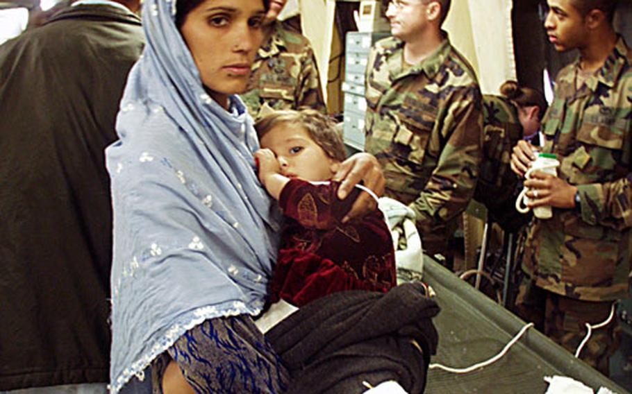 Aribba Abbasi, 2, is held by her mother in the 212th MASH in Muzaffarabad, Pakistan. Aribba's parents walked for two days to ask doctors to check her broken leg, an injury from the Oct. 8 earthquake. She and an 8-year-old boy were the MASH's first patients Tuesday morning, the day after the unit arrived.