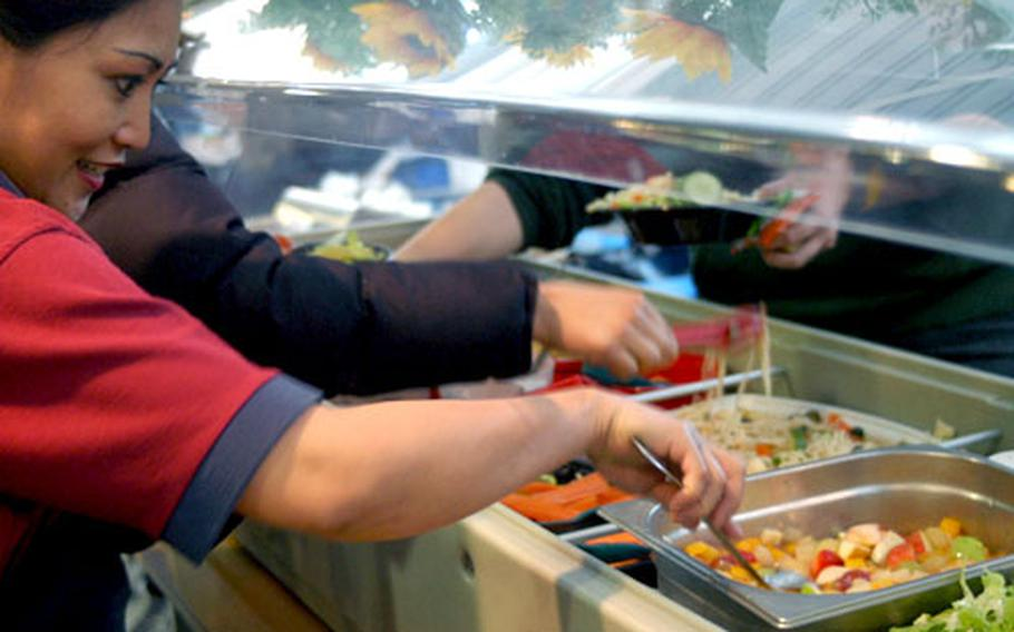"""Lakenheath's """"salad lady"""" Naneth Melcher keeps watch over her beloved salad bar, which she spends each lunch keeping stocked and tidy as students and teachers move through for some greenery."""